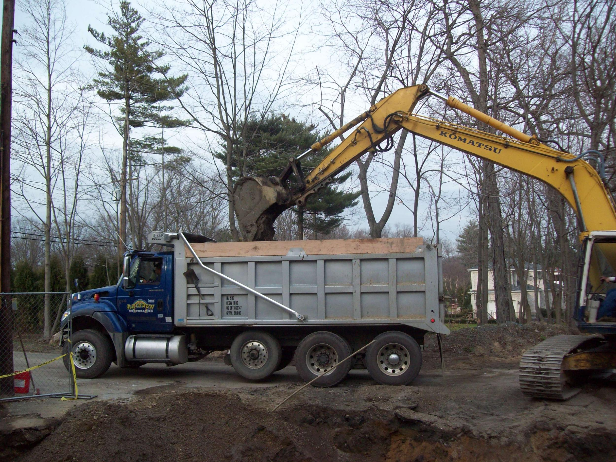Excavator loading soil into a dump truck